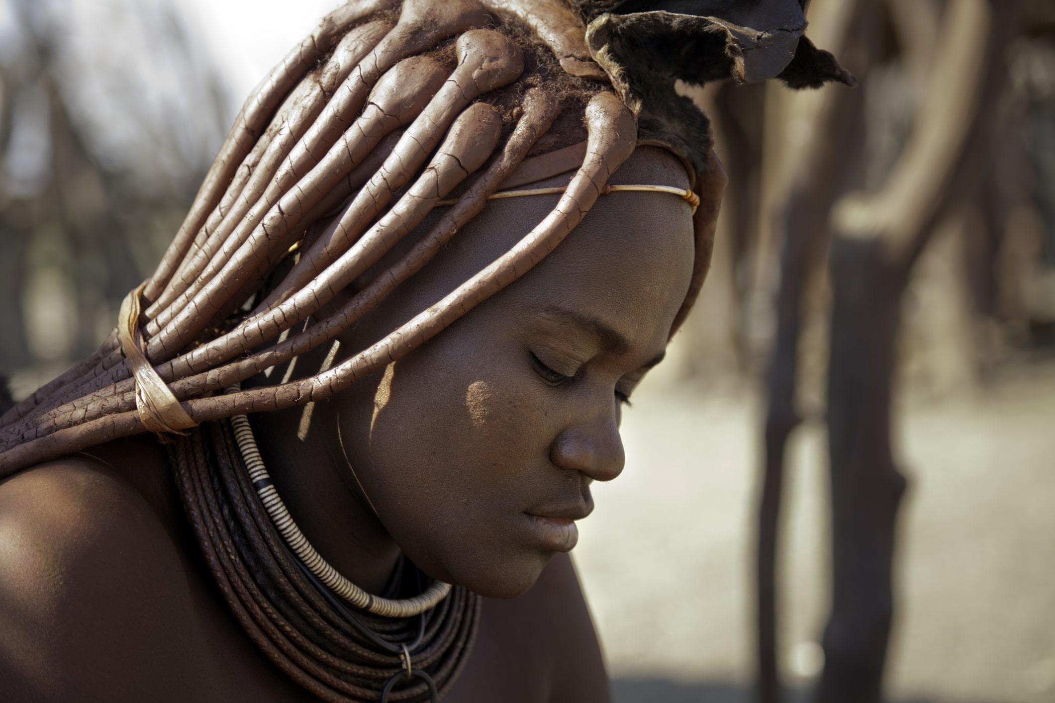 Die Frauen der Himba in Namibia sind bekannt für ihre Haare mit geflochtenen und rot eingecremten Strähnen.