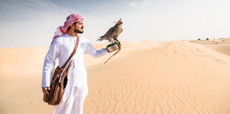 Ein Mann in der Wüste im Oman mit traditioneller Kleidung.