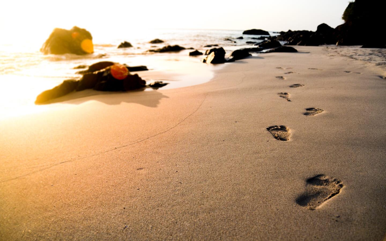 Fußabdrücke am Strand auf einer Urlaubsreise.