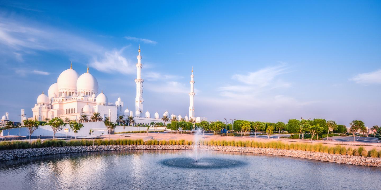 Die große Scheich-Zayid-Moschee in Abu Dhabi mit einem Springbrunnen im Vordergrund.
