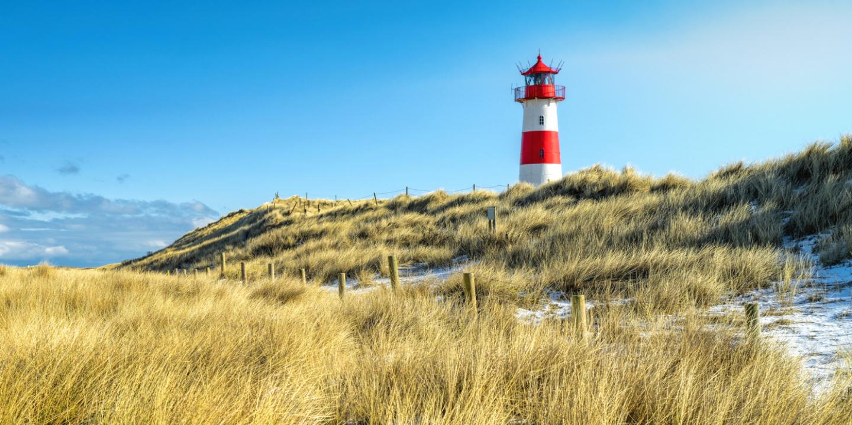 Ein typischer Leuchtturm am Strand, den man bei einem Nordsee-Urlaub zu sehen bekommt.