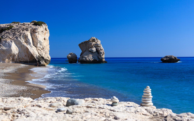 Der naturbelassene Kieselstrand Petra tou Romiou mit seiner beeindruckenden Felsformation gehört zu Zyperns schönsten Stränden.