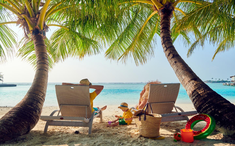 Ein Familienurlaub auf den Malediven unter Palmen am Strand.