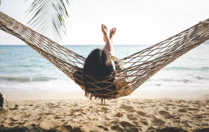 Eine Frau in einer Hängematte am Strand - 10 Gründe Ihren Urlaub für 2021 zu buchen.