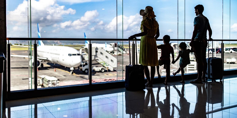 Eine Familie mit Kindern vor dem Abflug am Flughafen.