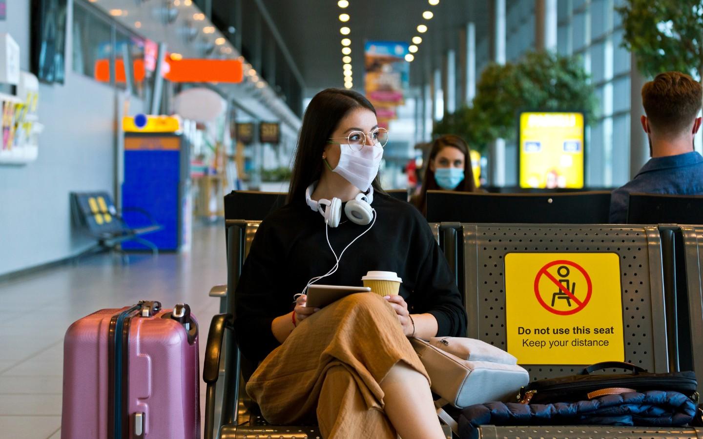 Eine Frau mit Mund-Nasenschutz am Flughafen.
