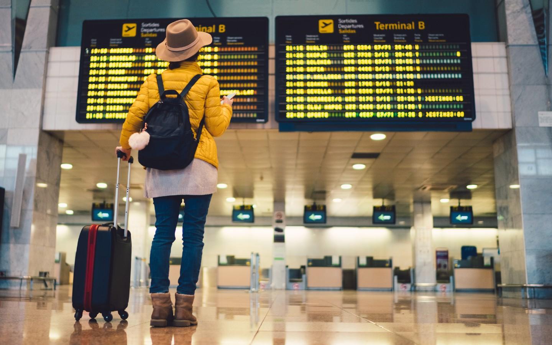 Eine Frau mit Reisekoffer am Flughafen.