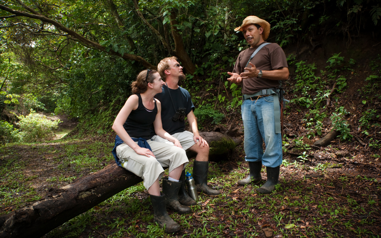 Zwei Touristen mit einem Tourguide auf einer nachhaltigen Reise in den Regenwald.