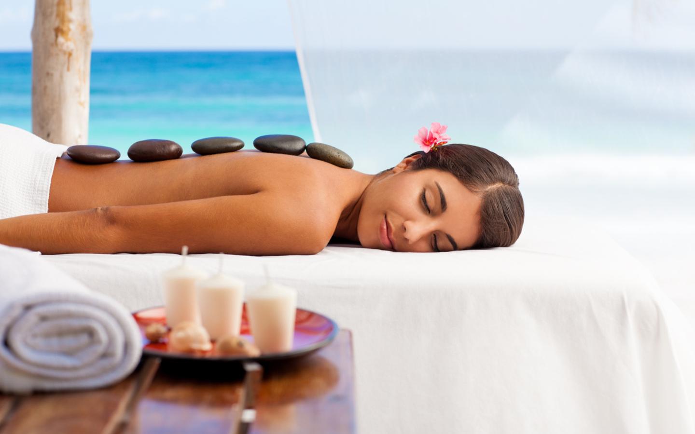 Eine Frau bekommt eine Massage am Strand im Indischen Ozean.