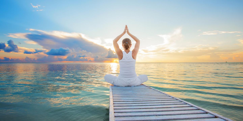 Eine Frau macht Yoga bei einem Wellnessurlaub im Indischen Ozean.