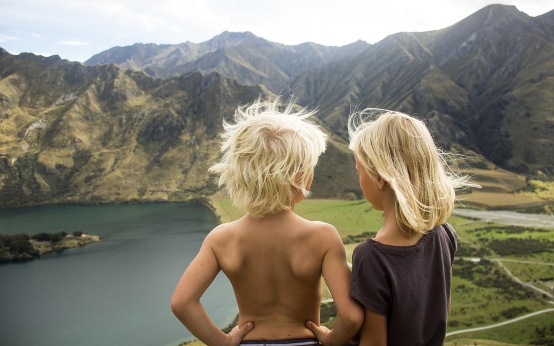 Zwei Kinder einer Familie in einer bergigen Landschaft auf ihrer Weltreise.