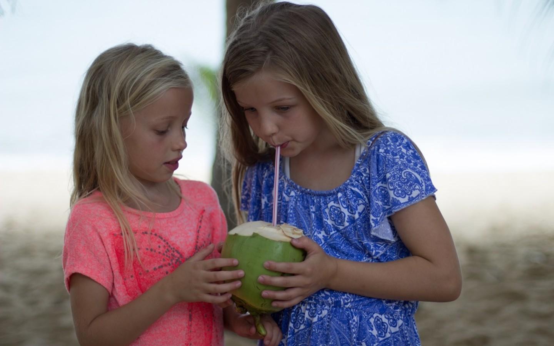 Zwei Kinder der Familie trinken aus einer exotischen Frucht auf Weltreise.