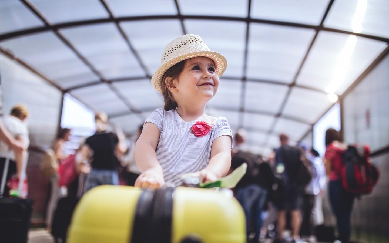 Ein Kind mit einem Reisekoffer vor dem Abflug auf die Seychellen.