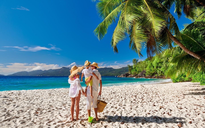 Eine Familie mit Kind am Strand auf den Seychellen.