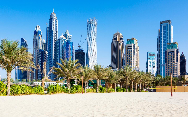 Ein Strand in Dubai mit der Skyline im Hintergrund.